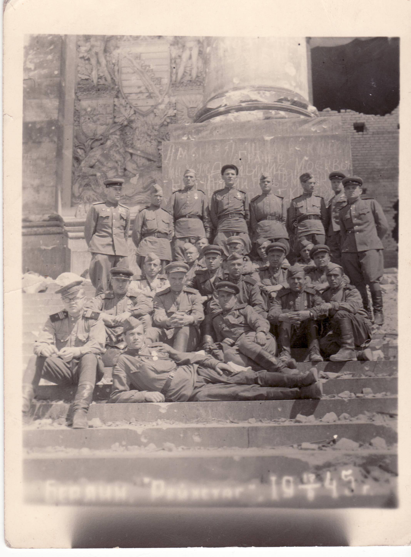 Лысенко Василий Тимофеевич, старший сержант, сидит в фуражке под центральным военным (с медалями), половина его лица скрыта пилоткой ниже сидящего солдата